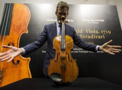 Staff member puts the 'Macdonald' viola made by Italian artisan Stradivari on a stand during a preview at Sotheby's gallery in Hong Kong
