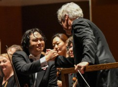 Pinchas Zukerman and NACO concertmaster Yosuke Kawasaki exchange a handshake. (Fred Cattroll photo)