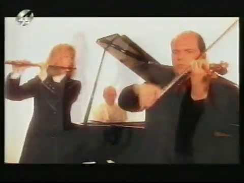 Two violinists mess around with dancers