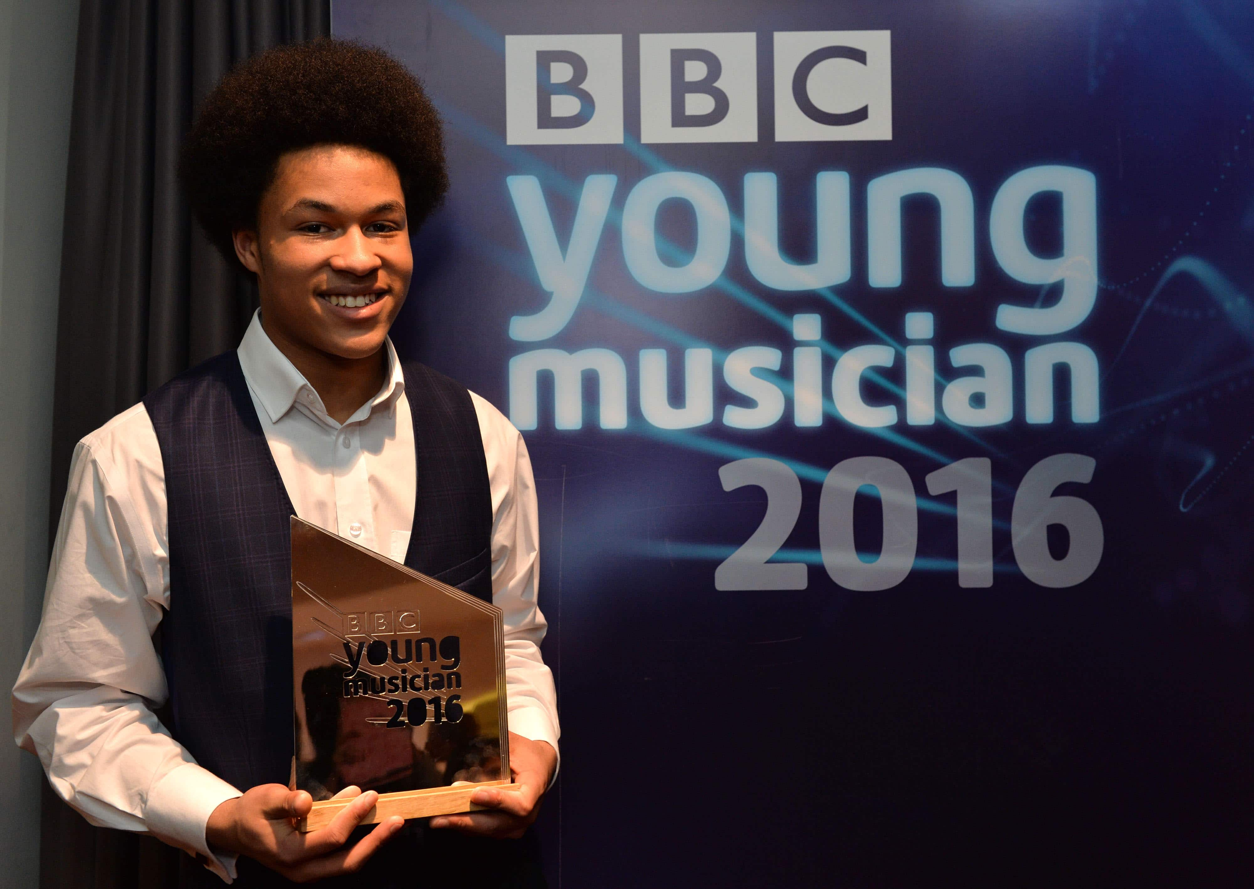 The winner of BBC Young Musician 2016, 17-year-old cellist Sheku Kanneh-Mason with his award at the Barbican, London on Sunday 15 May. Sheku performed ShostakovichÕs Cello Concerto no. 1 with the BBC Symphony Orchestra conducted by Mark Wigglesworth. The BBC Young Musician 2016 Final is broadcast on BBC Four at 7pm and BBC Radio 3 at 7:30pm on Sunday 15 May. Photo by Mark Allan/BBC