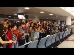 Watch: Youth orchestra is stranded at JFK airport, so they….