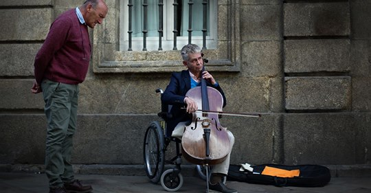 An injured orchestra cellist plays for pennies on the street